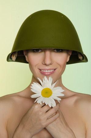 conscription: Young woman in a military helmet with chamomile
