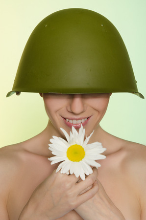 conscription: Smiling woman in the military helmet with chamomile