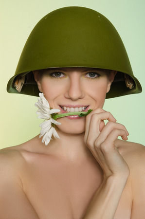 conscription: Young woman in military helmet with white a chamomile mouth