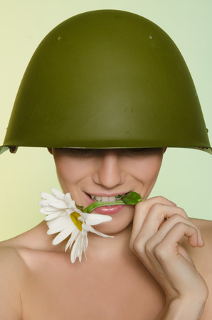 conscription: Young woman in a military helmet bites chamomile