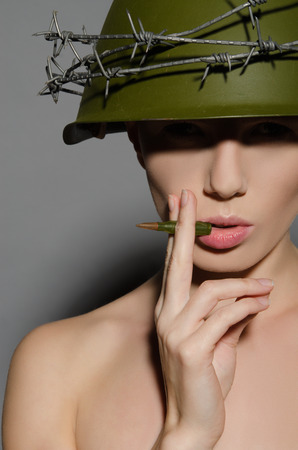 conscription: Female soldier in military helmet smokes bullet