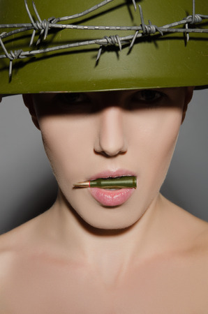 conscription: Female soldier in military helmet holding in his mouth a bullet