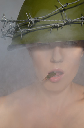 conscription: Young woman is holding in his mouth a bullet in the smoky background