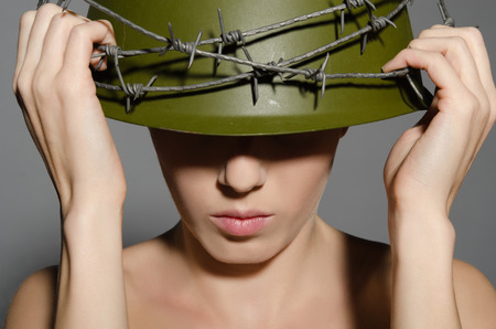 conscription: Young woman holding hands military helmet with barbed wire