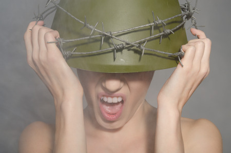 conscription: young woman the military helmet with barbed wire screams