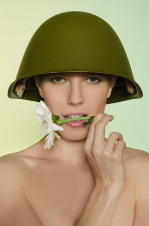 conscription: Beautiful woman in a military helmet with chamomile mouth