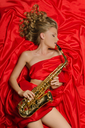 Woman in red enjoys playing the saxophone photo