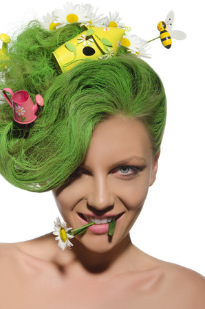 Woman with green hair in disorder and chamomile in mouth photo