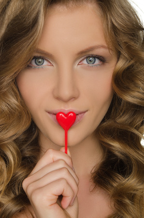 frizz: Beautiful woman holding a red heart in mouth Stock Photo