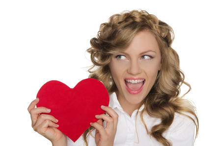 emote: Beautiful young woman holding heart next to him and looks away Stock Photo