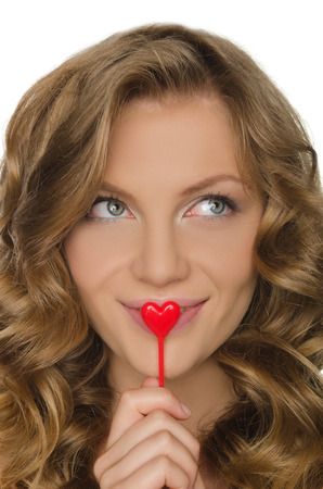 frizz: Beautiful young woman holding heart in front lip
