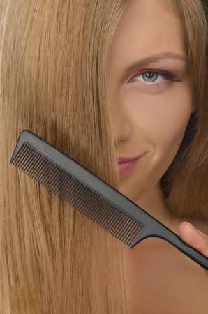 emote: beautiful young woman holding comb straightened hair Stock Photo