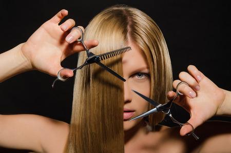 tijeras: Mujer hermosa joven con el pelo liso y tijeras sobre fondo negro