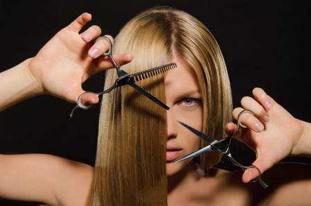 scissors: Young beautiful woman with straight hair and scissors on black background