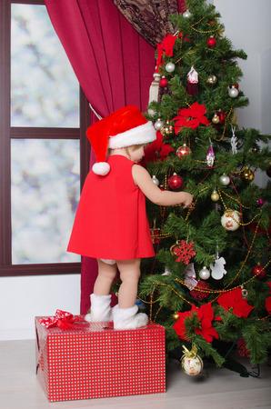 decorates: small child dressed as Santa decorates Christmas tree Stock Photo