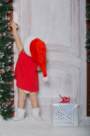 baby open present: Child dressed as Santa with gift opens door for Christmas