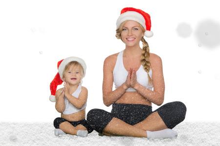ejercicio aer�bico: mujer con el ni�o que hace yoga en sombreros de la Navidad bajo la nieve que cae