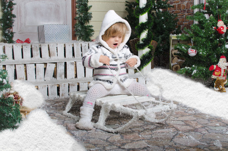 small child on sled in yard of winter snow photo