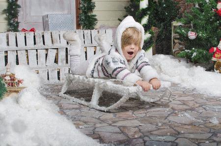 small child sledding in yard of winter snow photo