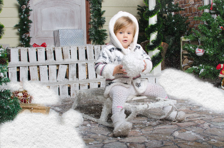 small child sits on sled with snow in hands photo