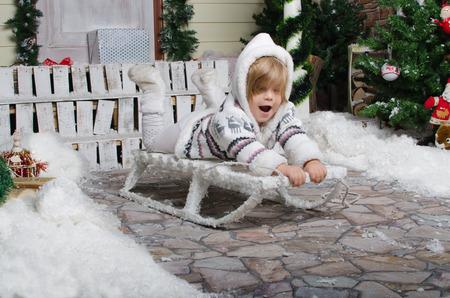 smiling child sledding in yard of winter snow photo