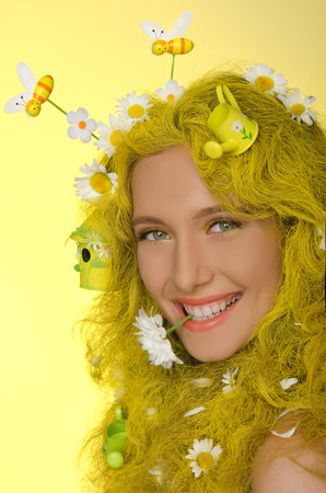 pleasantness: Young beautiful woman with yellow hair, flowers, and bees in them Stock Photo