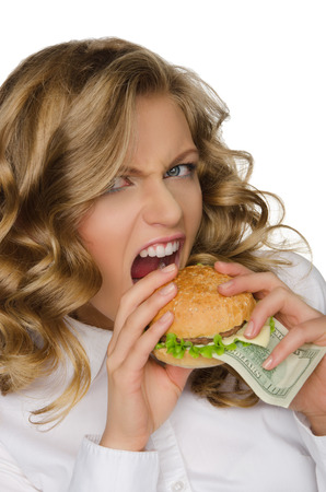 spite: Hungry young woman with burger of dollars isolated on white Stock Photo