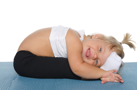 gymnastique: Petite fille faire de la gymnastique sur le tapis bleu