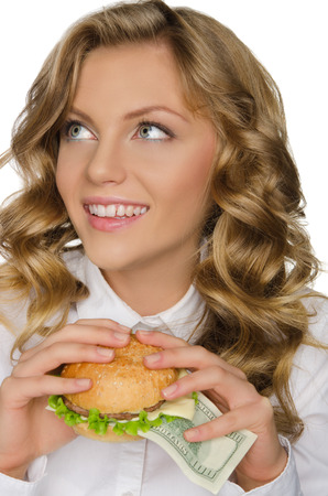 pleasantness: Young woman with burger of dollars looking away isolated on white