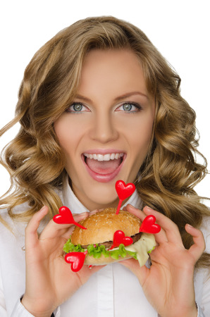 pleasantness: Smiling young woman with hamburger with hearts isolated on white Stock Photo