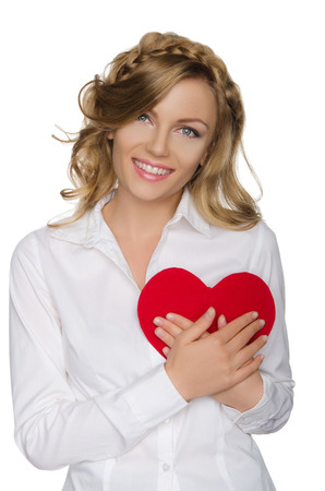 pleasantness: Beautiful blonde pushes heart to himself isolated on white