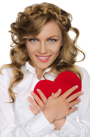 pleasantness: smiling woman pushes heart to himself isolated on white