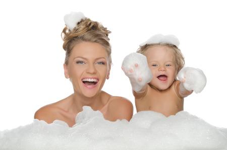 baÑo: Madre feliz con su hija y espuma de jabón aislado en blanco