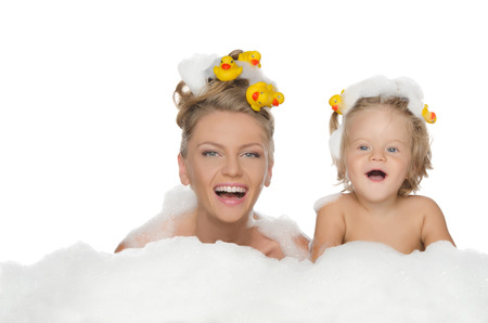 Young mother, daughter with ducks and soap foam isolated on white