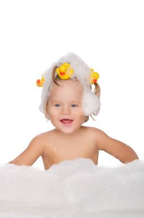 Smiling girl with ducks and soap foam isolated on white