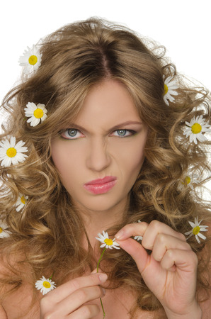 frizz: unhappy woman with daisies in curly hair takes petals Stock Photo