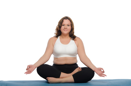 pleasantness: overweight woman practices yoga on blue mat Stock Photo