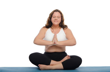 pleasantness: woman with overweight is meditating on blue mat Stock Photo