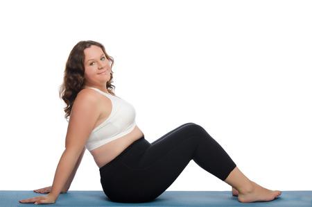 mujer cuerpo entero: mujer gorda con sobrepeso implicada en aptitud en la alfombra azul Foto de archivo