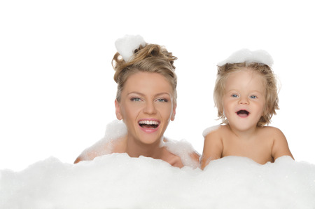 Young mother with her daughter and soap foam isolated on white Reklamní fotografie