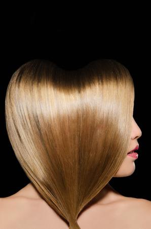 capelli lunghi: Bella acconciatura bionda in forma di cuore su sfondo scuro Archivio Fotografico