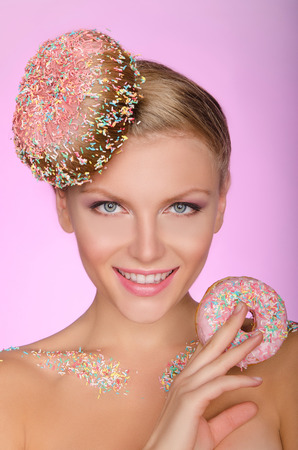 young woman with creative hairstyle from donut on pink background photo