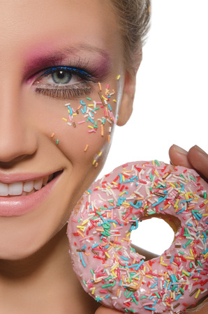 pleasantness: beautiful woman with confectionery decorations on face and donut on white background