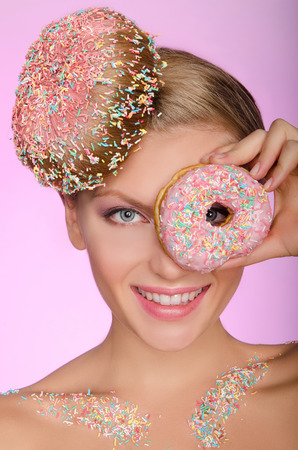 pleasantness: Beautiful woman with donut on head and in front of eye on pink background