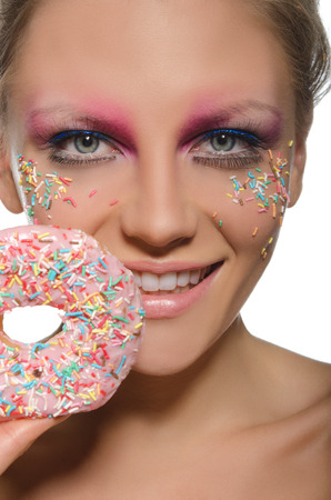 charming young woman with donut in mouth on white background photo