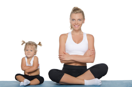 pleasantness: Mom and daughter engage in fitness on blue mat Stock Photo