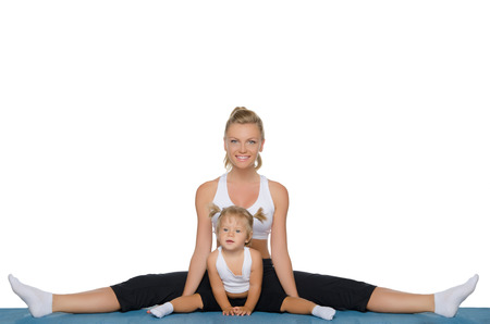 Mom and daughter do gymnastics on blue mat Stock Photo
