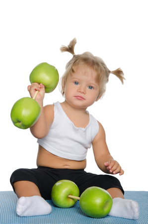 sport training: Little girl with weights of green apples isolated on white