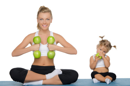 daughter mother: Mom and daughter engage in fitness dumbbells of green apples Stock Photo