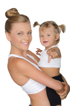 Smiling mother with her daughter in yoga clothes isolated on white Stock Photo